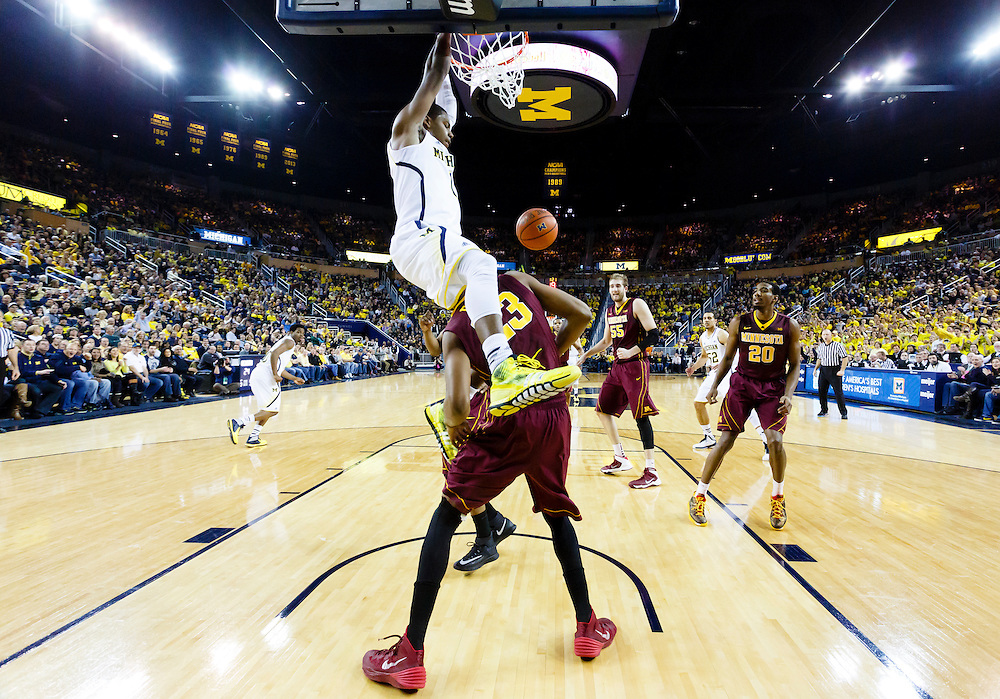 Mar 1, 2014; Ann Arbor, MI, USA; Michigan Wolverines forward Glenn Robinson III (1) dunks on Minnesota Golden Gophers forward Charles Buggs (23) in the first half at Crisler Arena. Mandatory Credit: Rick Osentoski-USA TODAY Sports