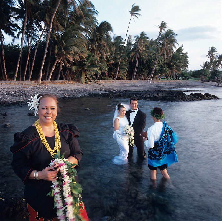 Wedding coordinator, Pinky Crowe, of the Mauna Lani Bay Hotel and Bungalows, Kaku(priest) and wedding couple in background.  Ceremony performed in the water