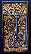 Calligraphy.  Square tile with holy names, Iran, 1400-1500.  Fritware, with decoration in coloured glazes.  It is inscribed with the names of Allah, the prophet Muhammad and his son-in-law and successor Ali in square Kufic script. Calligraphy panel, possibly from a cenotaph, Iran 1400-1500.  Wood with carved decoration.