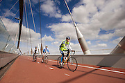 In Nijmegen rijden drie racefietsers op het fietspad aan de Oversteek, de nieuwe verbinding over de Waal aan de noordkant van Nijmegen.<br /> <br /> In Nijmegen cyclists are riding at the bike line at The Crossing, the new connection crossing the Waal at the north side of Nijmegen.