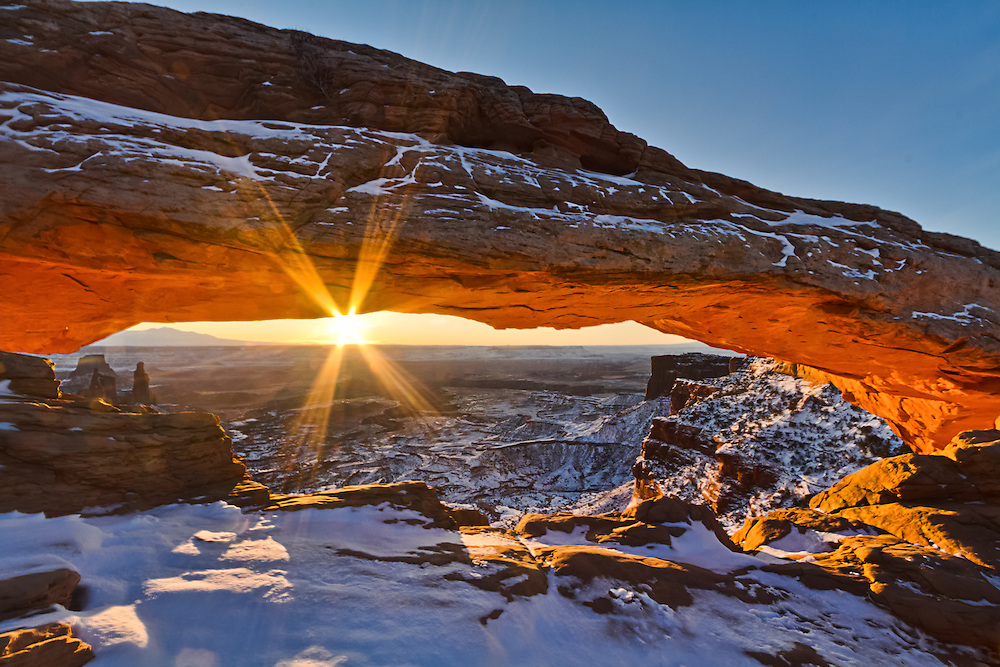 Mesa Arch covered in snow during a Winter sunrise with a sun star in Canyonlands National Park.