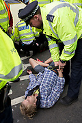 On the 10th consecutive day of protests around London by the climate change campaign Extinction Rebellion, police officers arrest an activist under Section 14 of the Public Order Act, on 24th April 2019, at Marble Arch, London England.