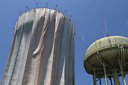 Like a giant Christo art installation, protective curtains hang from newly-built water tower during spray painting; Kirkwood, Missouri.