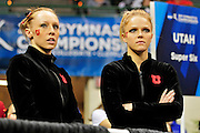 University of Utah seniors Jacquelyn Johnson, left, and Gael Mackie at  watch as the University of Alabama is interviewed after taking first place at the 2011 Women's NCAA Gymnastics Championship Team Finals on April 16, in Cleveland, OH. The Utes took fifth. (photo/Jason Miller)