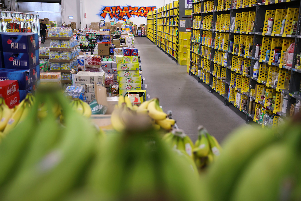 Shelves stand stacked with items across from cases of beverages and fresh bananas at the Amazon.com Inc. Prime Now fulfillment center warehouse on Monday, March 27, 2017 in Los Angeles, Calif. The warehouse can fulfill one and two hour delivery to customers. Complex supply chains such as Amazon's and e-commerce trends will impact city infrastructure and how things move through cities. © 2017 Patrick T. Fallon