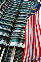 Close up of the Petronas Twin Towers with a Malaysian flag in the foreground.