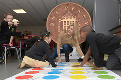 Image ©Licensed to i-Images Picture Agency. 18/12/2014. London, United Kingdom. <br /> <br /> Penny Lancaster visits Charlton Manor Primary School where the Mayors Fund initiative 'Penny for London' is raising money to fund breakfasts for school children.<br /> <br /> Penny Lancaster plays Twister with children at breakfast club.<br /> <br /> Picture by Ben Stevens / i-Images