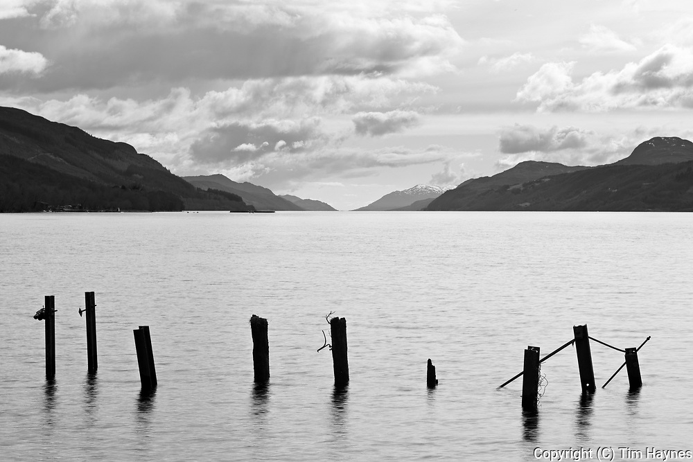 A view down the length of Loch Ness from beside the pub at Dores, with the remaining posts of a ruined jetty in the foreground.