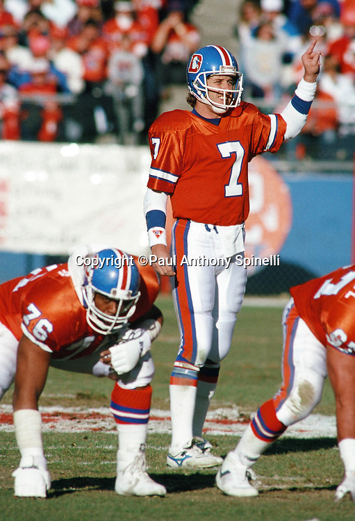 Denver Broncos quarterback John Elway (7) points as he gets set to call signals over center during the NFL AFC Divisional playoff football game against the Pittsburgh Steelers on Jan. 7, 1990 in Denver. The Broncos won the game 24-23. (©Paul Anthony Spinelli)