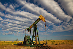 """Pumpjack in a rural Texas field and wind turbines on the horizon with blue sky and dramatic cloud formations called """"cloud streets""""."""