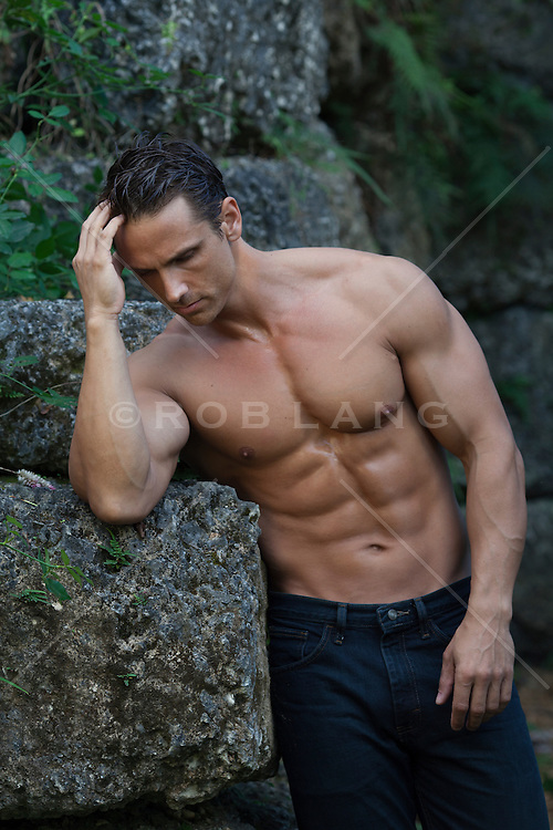man without a shirt with a muscular body leaning against large pieces of coral