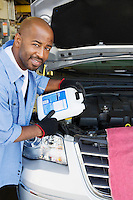 Auto Mechanic Adding Fluids to Minivan