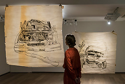 """© Licensed to London News Pictures. 20/11/2018. LONDON, UK. A staff member views (L to R) """"Car Crash 4"""", 2017, and """"Car Crash 3"""", 2017, both by Aysha Almoayyed.  Preview of """"Accumulation:  Legacy and Memory"""", an exhibition presented by Art Bahrain Across Borders during Bahrain Art Week.  Works from 11 emerging and established Bahraini artists is on display 20th to 26 November at Alon Zakaim Fine Art gallery in Mayfair.  Photo credit: Stephen Chung/LNP"""