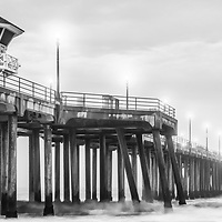 Panoramic picture of Huntington Beach Pier in black and white. Huntington Beach is a popular surfing destination also known as Surf City USA. Huntington Beach is located along the Pacific Ocean in Orange County Southern California in the United States.