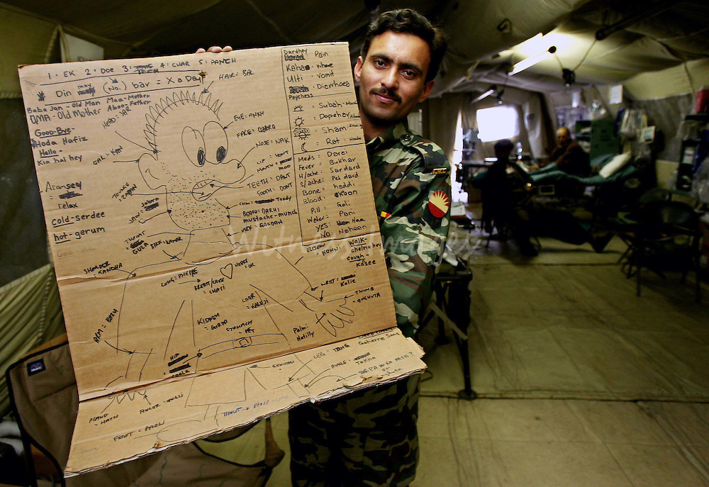 Pakistani Army operating technician Munawar holds up a drawing which translates the names of parts of the body from English to Urdu at the U.S. 212th Mobile Army Surgical Hospital (MASH) in the earthquake-devastated city of Muzaffarabad, in Pakistan-administered Kashmir February 15, 2006. U.S forces will hand over its last field hospital unit to the Pakistani Army's 67th Medical Battalion for the continuation of relief and rehabilitation works on Thursday. Winter weather has made life more difficult for survivors of last year's massive earthquake in South Asia, where more than two million people have been living in tents or crude shelters patched together from ruined homes. REUTERS/Thierry Roge