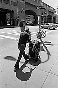 During the hot Summer heat a woman pushes her laundry down Queens Boulevard.