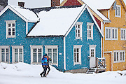 Couple walk past traditional wooden buildings along Storgata in the quaint area of Tromso, in the Arctic Circle in Northern Norway