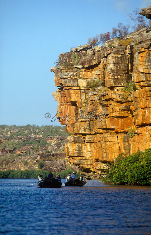 Adventure travelers exploring the rugged sandstone walls of the King George River in Zodiac rafts. Kimberley, W. AUSTRALIA