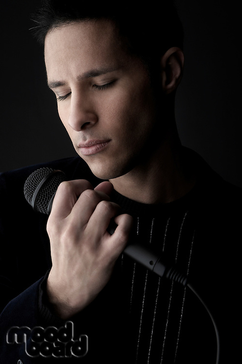 Young man holding microphone close-up
