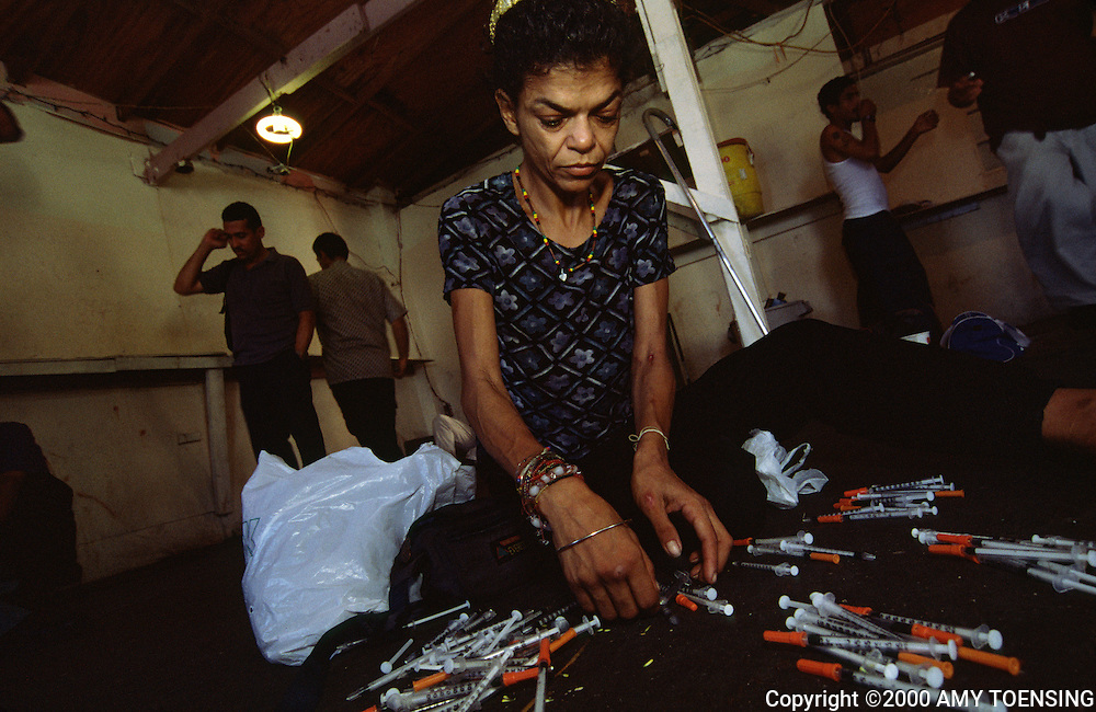 OLD SAN JUAN, PR - NOVEMBER 14: A drug user presents her used needles to be exchanged for clean, new needles by Iniciativa Comunitaria, an HIV/drug assistance program in a shooting gallery in the La Perla neighborhood November 14, 2001 in Old San Juan, Puerto Rico. Puerto Rico was an outpost of Spanish colonialism for 400 years, until the United States took possession in 1898. Today Puerto Rico's Spanish-speaking culture reflects its history - a mix of African slaves, Spanish settlers, and Taino Indians. Puerto Ricans fight in the U.S. armed forces but are not entitled to vote in presidential elections. They passionately debate their relationship with the U.S. with about half the island wanting to become the 51st state and the other half wanting to remain a U.S. commonwealth. A small percentage feel the island should be an independent country. While locals grapple with the evils of a burgeoning drug trade and unchecked development, drumbeats still drive the rhythms of African-inspired bomba music. (Photo By Amy Toensing) _________________________________<br />