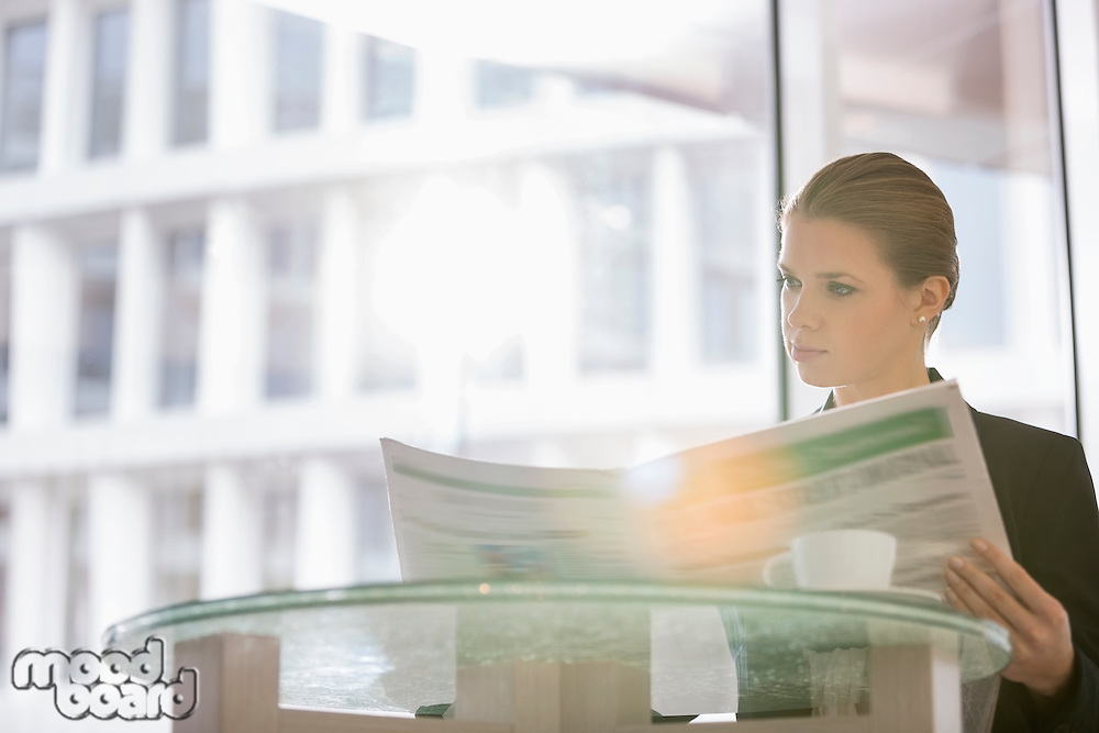 Businesswoman reading newspaper at office cafeteria