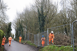 Harefield, UK. 14 January, 2020. Enforcement agents erect fencing around woodlland close to a protection camp from which Stop HS2 activists are being evicted. Part of the nearby Colne Valley protection camp was evicted by bailiffs last week. 108 ancient woodlands are set to be destroyed by the high-speed rail link and further destruction of trees for HS2 in the Harvil Road area is believed to be imminent.