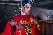 "25 JANUARY 2014 - BANG LUANG, NAKHON PATHOM, THAILAND: A performer with the Sing Tong Teochew opera troupe gets into character before a show in a Chinese shrine in the town of Bang Luang, Nakhon Pathom, Thailand. The Sing Tong Teochew opera troupe has been together for 60 years and travels through central Thailand and Bangkok performing for mostly ethnic Chinese audiences. Chinese opera was once very popular in Thailand, where it is called ""Ngiew."" It is usually performed in the Teochew language. Millions of Chinese emigrated to Thailand (then Siam) in the 18th and 19th centuries and brought their cultural practices with them. Recently the popularity of ngiew has faded as people turn to performances of opera on DVD or movies. There are still as many 30 Chinese opera troupes left in Bangkok and its environs. They are especially busy during Chinese New Year when travel from Chinese temple to Chinese temple performing on stages they put up in streets near the temple, sometimes sleeping on hammocks they sling under their stage.     PHOTO BY JACK KURTZ"