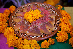 "North America, Mexico, San Miguel de Allende, special ""Pan de Muertos"" bread and marigolds at altar for Day of the Dead celebration, also known as Dios de los Muertos.  Mexicans celebrate the Day of the Dead on November 1st and 2nd in connection with the Catholic holy days of All Saints' Day and All Souls' Day."