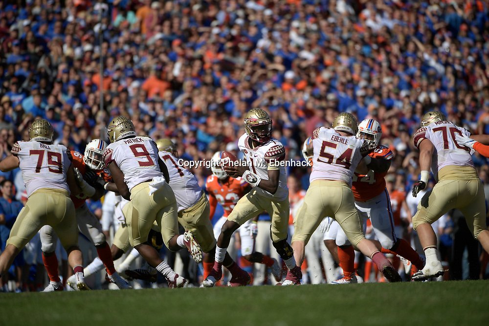 Florida State quarterback James Blackman (1) rolls out behind the offensive line during the first half of an NCAA college football game against Florida Saturday, Nov. 25, 2017, in Gainesville, Fla. (Photo by Phelan M. Ebenhack)