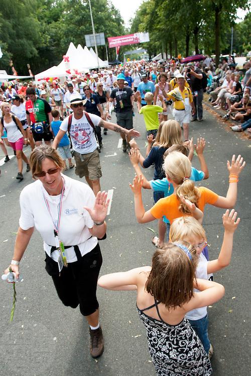 Wandelaars van de Nijmeegse Vierdaagse lopen op de laatste dag over de Via Gladiola, zoals de Sint Annastraat is omgedoopt tijdens het wandelevenement.