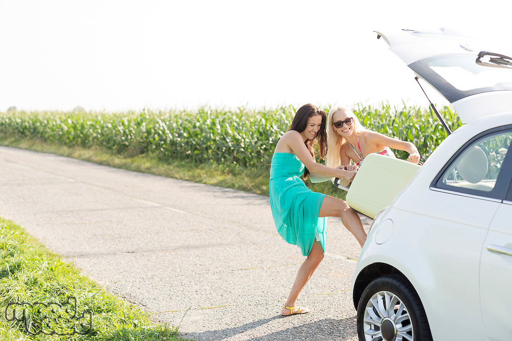 Happy female friends pushing luggage in car trunk against clear sky