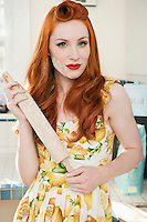Portrait of a confident redheaded woman holding a rolling pin