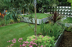 General view showing three floating steel trays creating different levels of lawn and planting. Workshop clad with aluminium reflective disks. Eucalyptus and cordyline in foreground. Design Diarmuid Gavin