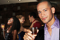 Young man holding drink standing in bar portrait
