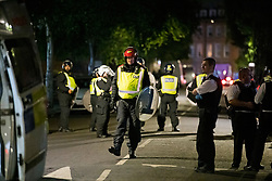 © Licensed to London News Pictures. 26/06/2020. London, UK. Police in riot equipment attempt to disperse an illegal Street Party at Riverton Close in Maida Vale, West London.  A number of similar events have occurred across the capital, with some resulting in violence towards police. Photo credit: Ben Cawthra/LNP