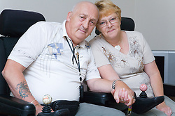 Disabled couple at home holding hands with one another,