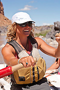 River Guide Kelly Wagner rowing her raft on the Colorado River in Westwater Canyon Utah.