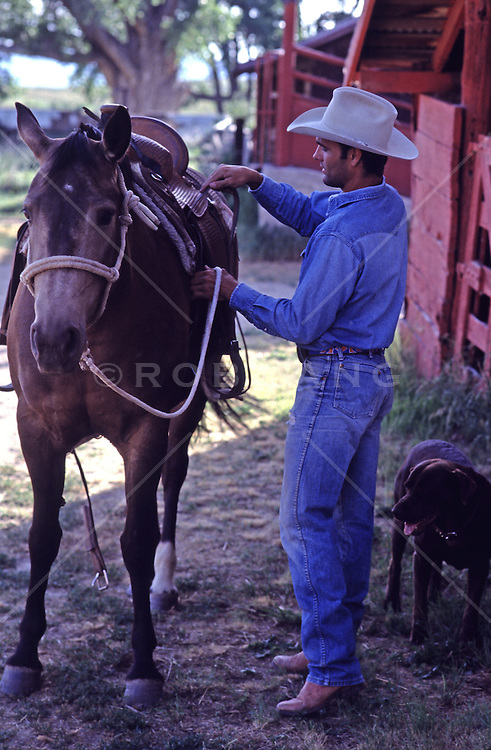 cowboy brushing a horse by a barn