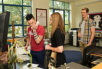Justin Spencer and Ryan Vezina of Recycled Percussion take control of the intercom from Principal Bryant to announce a school wide takeover on Thursday afternoon.   (Karen Bobotas/for the Laconia Daily Sun)