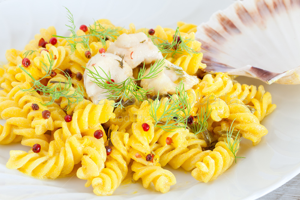 Closeup of plate with seafood pasta prepared with fusilli, scallops and fresh dill.