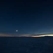 Wide-angle landscape during the darkness of totality, with the shape of the moon's shadow clearly visible in the darkened sky, with light at its edge on the horizon, 20 March 2015, Svalbard, Norway