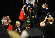 A doctoral graduate is hooded on stage at the Graduate Commencement.