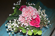 Artificial bouquet of carnation and rose flowers sitting on deck bench.  Plymouth Minnesota USA