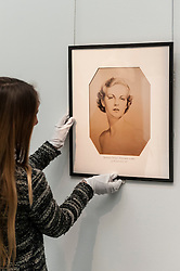 © Licensed to London News Pictures. 26/02/2016. London, UK. A Sotheby's staff member hangs a portrait of the Duchess.  Property from the personal collection of Deborah, Duchess of Devonshire (1920-2014), will be offered for sale at Sotheby's on 2 March,  The youngest of the Mitford Sisters, the Duchess was the chatelaine of Chatsworth, one of England's greatest stately homes, and at the heart of British rural, cultural and political life.  The proceeds of the items in the eclectic collection are expected to realise £500,000 to £700,000. Photo credit : Stephen Chung/LNP