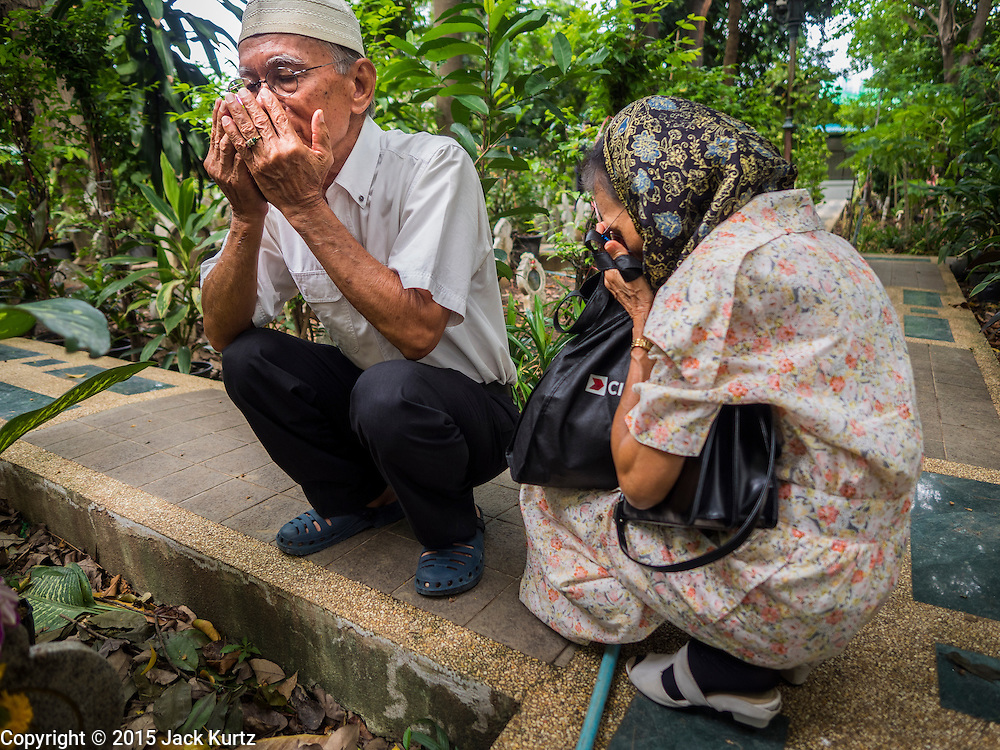 17 JULY 2015 - BANGKOK, THAILAND:     A man and his wife pray at the grave of her parents in the cemetery of Ton Son Mosque after Eid services at the mosque in Bangkok. Eid al-Fitr is also called Feast of Breaking the Fast, the Sugar Feast, Bayram (Bajram), the Sweet Festival or Hari Raya Puasa and the Lesser Eid. It is an important Muslim religious holiday that marks the end of Ramadan, the Islamic holy month of fasting. Muslims are not allowed to fast on Eid. The holiday celebrates the conclusion of the 29 or 30 days of dawn-to-sunset fasting Muslims do during the month of Ramadan. Islam is the second largest religion in Thailand. Government sources say about 5% of Thais are Muslim, many in the Muslim community say the number is closer to 10%.          PHOTO BY JACK KURTZ