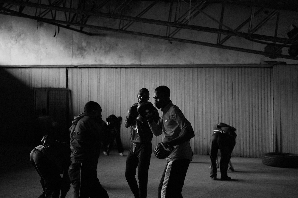 NAIROBI, KENYA - NOVEMBER 14, 2011: Members of the Kibera Olympic Boxing Club train for an upcoming bout at the Joseph Kangethe Social Hall in Kibera slum.<br /> <br /> Within Kenya's progressive youth culture is the Kibera Olympic Boxing Club, a group of low-income adolescents from the slum whose leader uses boxing as a way to engage with idle youth. The group's ethnic diversity is remarkable given Kenya's 2008 post-election violence in which people from several tribes were forced violently out of slums. Together, these boxers represent a nascent trend of cross-tribe brotherhood in a healing nation.