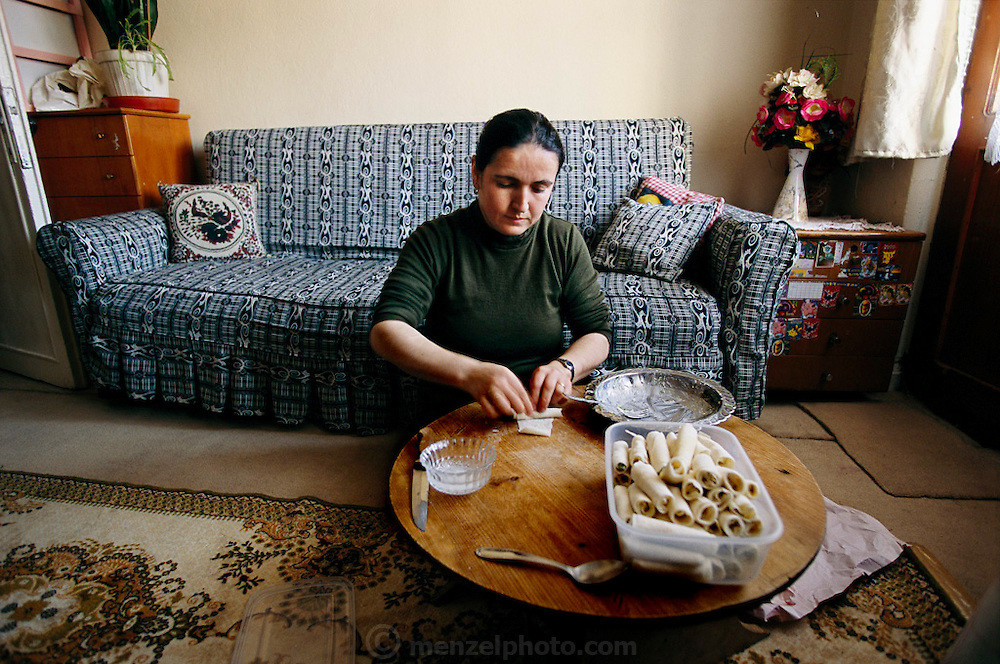 (MODEL RELEASED IMAGE). After Melahat Çelik mixes the arugula-feta filling for a savory Turkish pastry in her apartment kitchen, she sits on the living room floor and rolls paper-thin pastry called yufka around the filling to create an eggroll-style pastry her family loves. Hungry Planet: What the World Eats (p. 259).