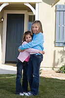 Portrait of girls (609) hugging in front of house