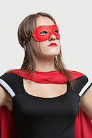 Young woman in superhero costume looking up over gray background