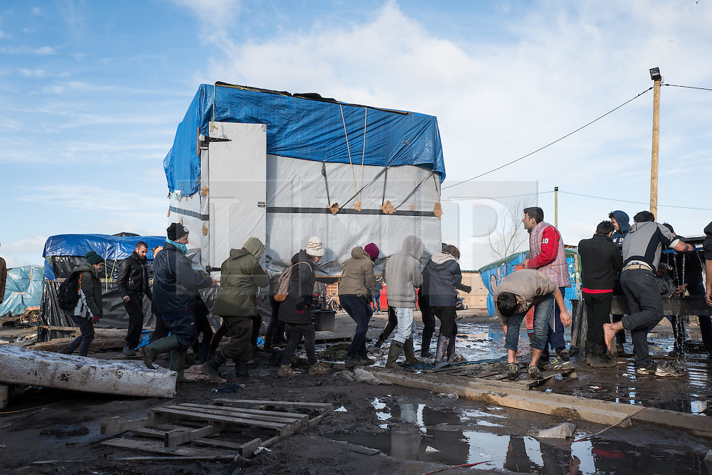 © London News Pictures. Calais, France. 15/01/16. Volunteers relocate a shelter, which would otherwise be destroyed, through the Calais 'Jungle' refugee camp. French authorities are to bulldoze a 100-metre 'buffer zone' between the camp and the adjacent motorway, which leads to the ferry port. Photo credit: Rob Pinney/LNP